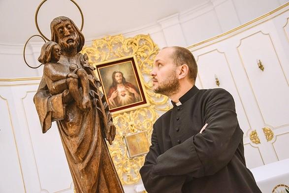 Ksiądz Marcin Gołębiewski i dębowa figurka św. Józefa z Dzieciątkiem.